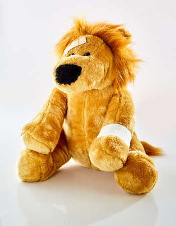 Ill plush toy lion with bandaged arm and patch on forehead. Pediatrician doctors office concept