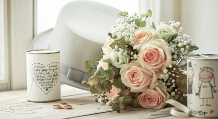 Bright composition for marriage day with wedding rings, bridal bouquet of pink roses, groom's white hat and cans with decorations and wishes on bright window sill