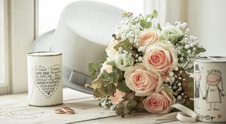 Helle Komposition für den Hochzeitstag mit Eheringen, Brautstrauß aus rosa Rosen, weißem Hut des Bräutigams und Dosen mit Dekorationen und Wünschen auf hellem Fensterbrett Standard-Bild