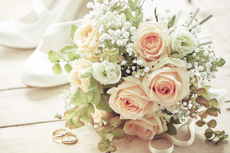 Marriage day setting with bridal bouquet of pink roses, white brides shoes and wedding rings  on wooden background