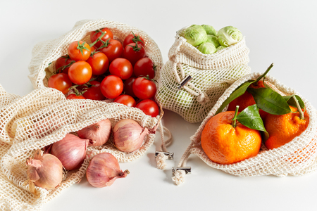Fresh organic groceries of fruits and vegetables packed in eco-friendly reusable net bags, viewed in close-up on white background