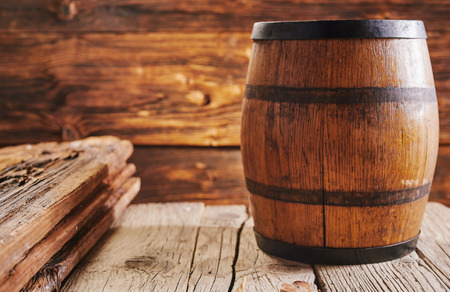 Lacquered barrel on old wooden boards surface with copy space, inside rustic house or bar