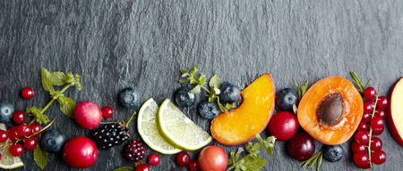 Banner concept with fresh fruit pieces and berries on dark grey stone background with wide copy space