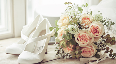 Bridal bouquet, pair of white shoes decorated with hearts and white hat. Wedding composition sitting on window sill in bright light, viewed in close-up