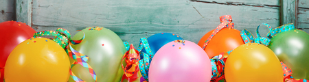 Festive banner with a row of colorful balloons and ribbons in a row against old wooden background