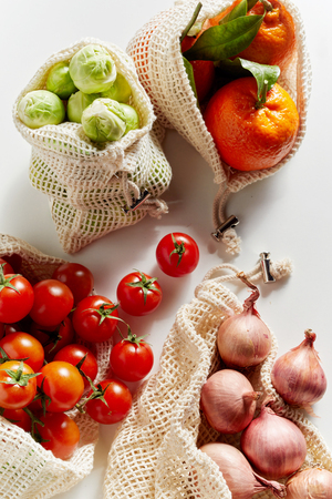 Top view of fresh organic groceries in reusable net bags. Tomatoes, Brussels sprouts, onion and oranges viewed from above