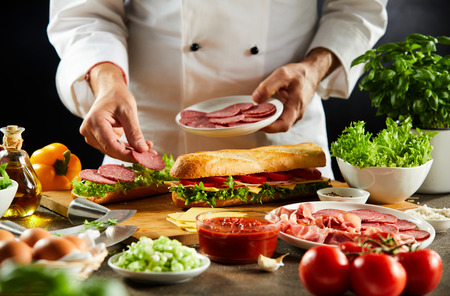 Chef preparing a crusty baguette sandwich with cold sliced salami and fresh salad