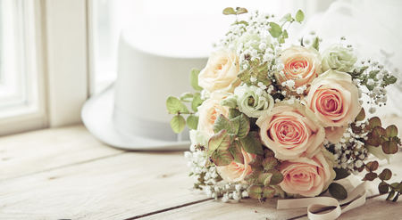 Broom white hat and bridal bouquet of pink roses in marriage day composition on wooden window sill with copy space