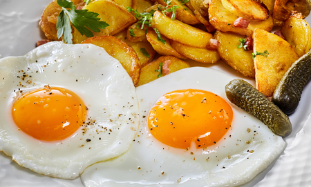 Two seasoned sunny side up fried eggs with vivid yellow yolks served with fried potato wedges and gherkin