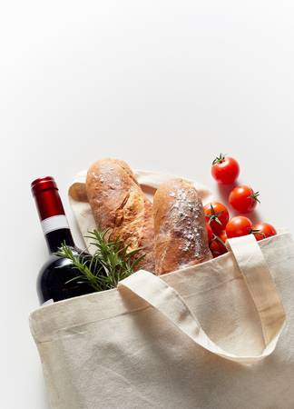 Eco-friendly white fabric bag filled with groceries, placed on white background with copy space