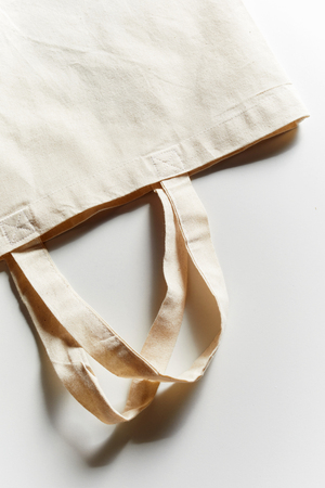 Unlabeled empty reusable eco-friendly fabric bag for groceries shopping, viewed in close-up from above on white background