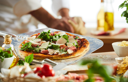 Metal pizzeria paddle with crusty Italian pizza topped with rocket, ham and cheese with foreground ingredients Standard-Bild