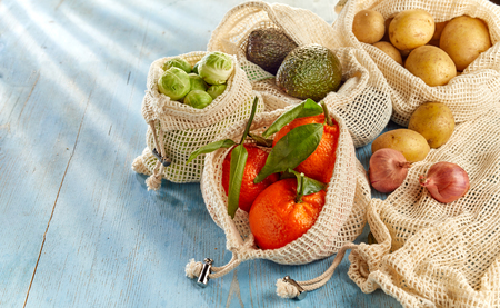 Groceries from country market, fresh fruits and organic vegetables in eco-friendly reusable net bags, placed on wooden table and viewed in close-up with copy space