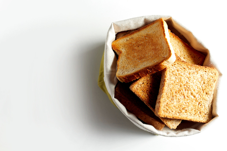 Fried toast bread slices put in white bag, and viewed from above on white background with shadow. Copy space
