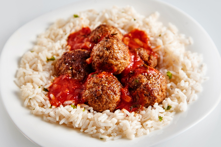 Serving of fried meatballs or frikadellen on a bed of long grain rice topped with a tomato sauce