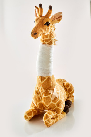 Plush toy giraffe with bandaged neck and patch, sitting on white background. Children health care concept Stock Photo