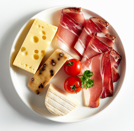 Variety of cheese, sliced bacon and fresh tomatoes served on white plate. Viewed from above in close-up