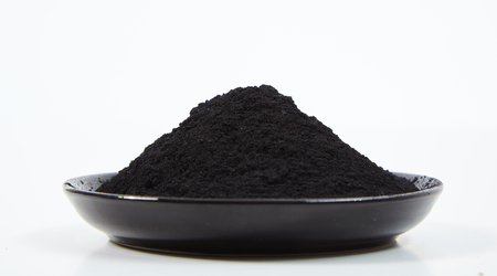 A pile of powdered charcoal on black plate, viewed from the side against white background 版權商用圖片