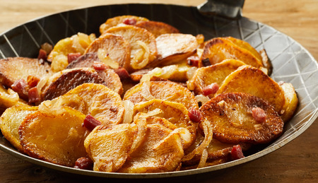Crispy fried potatoes in a black skillet served as a side dish in a restaurant Фото со стока
