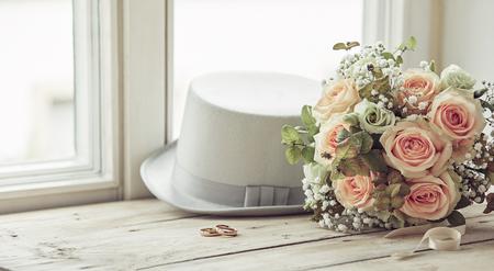 Composición del día del matrimonio del sombrero blanco del novio, anillos de boda y ramo de rosas rosadas, sentado en el alféizar de la ventana de madera