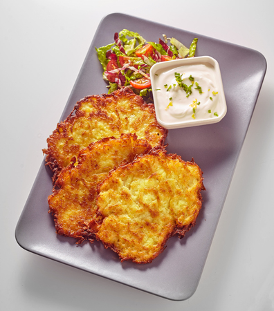 fried crispy Bavarian potato fritters served with a creamy dipping sauce and salad sides in a top down view