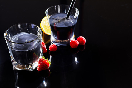 Two alcohol cocktail drinks with dark beverage on black counter, served with fresh berries and lemon. Stock Photo