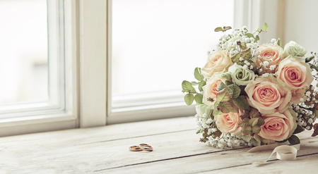 Pair of wedding rings and bridal bouquet of pink roses, sitting on bright window sill, before the ceremony