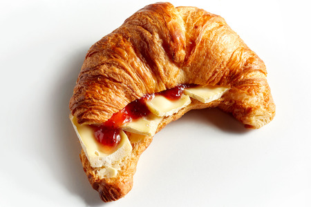Croissant sandwich with cheese and tomato ketchup, placed on white background and viewed in closeup