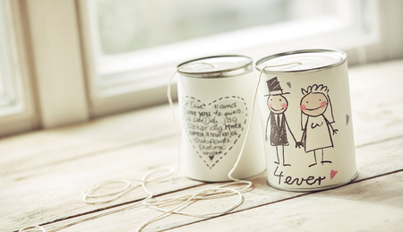 Decorated marriage cans with threads attached, heart shaped note with wishes and drawing of broom and bride on wooden window sill. Wedding ceremony concept Reklamní fotografie
