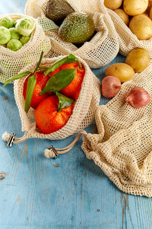Assortment of organic groceries in reusable eco-friendly net bags. Fresh oranges, avocados, Brussels sprouts, potatoes and onion on blue wooden table, viewed from above in close-up