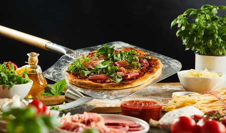Freshly baked pizza on a metal paddle in a pizzeria with fresh ingredients in the foreground Фото со стока - 116543423