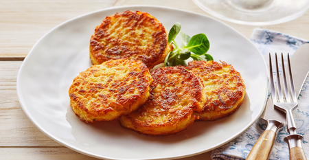 Plate of crispy golden fried potato fritters with watercress, a traditional German and Bavarian dish Stockfoto