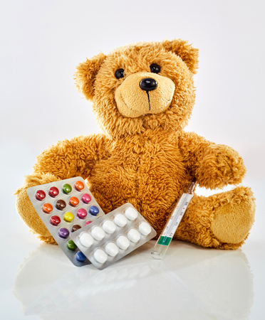 Toy bear with medicine, thermometer and colorful pills in blister pack, sitting on glossy surface against white background. Viewed from its front. Pediatrician office and children health concept