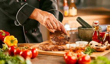 Chef assaisonnant un steak cru pour griller entouré d'ingrédients frais et de légumes en gros plan sur ses mains