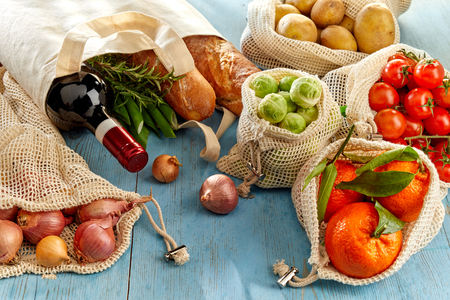 Bottle of wine, baguette and fresh organic groceries from local market in reusable eco-friendly fabric bags, viewed from high angle on blue wooden background