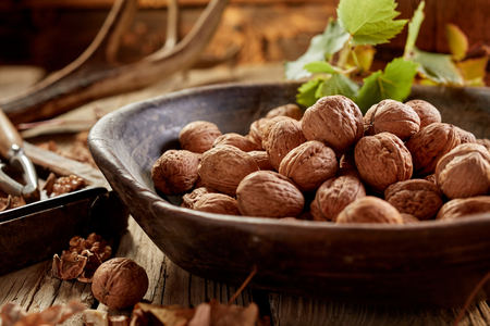 Walnuts in shells in wooden bowl in rustic hunters house on wooden table in close-up Stockfoto - 116540192