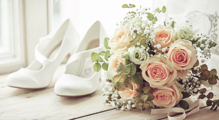 Bride's white shoes and beautiful wedding bridal bouquet of pink roses in close-up on wooden sill of bright window Zdjęcie Seryjne - 116540205
