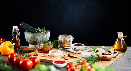 Herbs, spices and fresh ingredients for Italian cuisine on a kitchen counter with olive oil and a pestle and mortar against a black background with copy space in a panorama banner