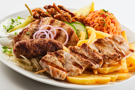 Assorted grilled meat with fried potato chips, savory rice and salad served on a plate in a close up view of regional Greek cuisine Imagens