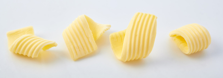 Set of different butter curls or rolls in a row in close-up on white surface background