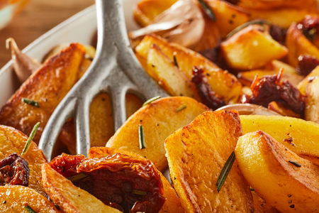 Pan fried rosemary potato wedges with an old metal spatula in a close up full frame view