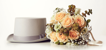 Wedding bouquet of roses and grooms hat in close-up from the side against white background, ready for marriage ceremony