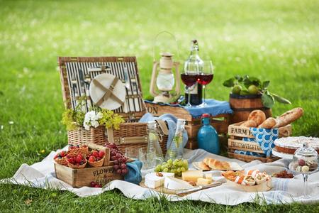 Picknickkorb aus Korbgeflecht mit verschiedenen frischen Speisen, aufgegossenem Wasser und Wein auf einem Teppich, der auf dem grünen Gras in einem Park ausgebreitet ist