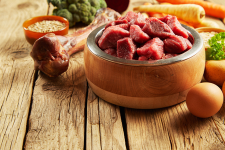 Pet food in a wooden bowl with fresh meat, bone, egg and vegetables for a healthy diet for carnivores such as cats and dogs Фото со стока