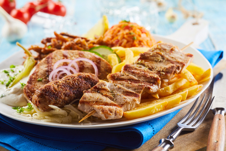 Grilled assorted meat on a plate with fried potato chips, savory rice, salad and onion rings for a tasty Greek dinner in a close up view