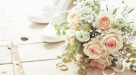 Composición del día del matrimonio con zapatos, rosas rosas flores ramo de novia y anillos de boda vistos desde un ángulo alto sobre fondo de madera