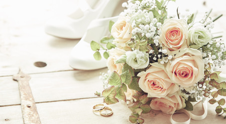 Marriage day composition with shoes, pink roses flowers bridal bouquet and wedding rings viewed from high angle on wooden background Foto de archivo
