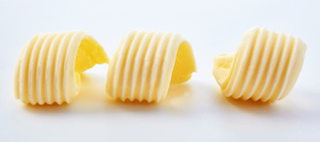 Three butter curls viewed in close-up on white surface background