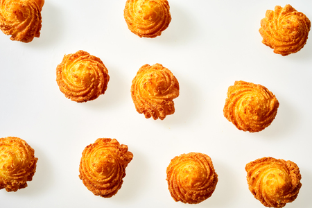 Deep fried decorative twirls of crispy potato scattered over a white  viewed from above