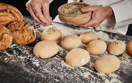 Baker sprinkling crushed grain and seeds on buns dough already formed into buns or rolls on a floured kitchen counter Imagens